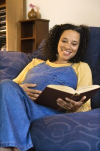 Pregnant smiling woman reading.